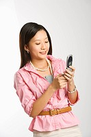 Portrait of Asian Chinese mid_adult female smiling and text messaging on cell phone