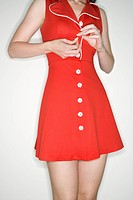 Caucasian young adult woman buttoning retro dress