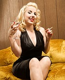 Attractive Caucasian woman holding a martini and cigarette.
