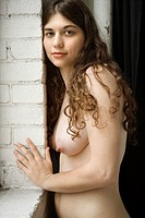 Nude Caucasian young woman leaning against brick wall looking at viewer