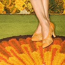 Close-up of female feet wearing orange shoes against colorful retro rug.