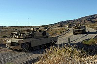 M1A1 Abrams main battle tanks advance up the road