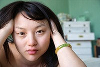Portrait of pretty young Asian woman lying in bed with hands in hair making eye contact