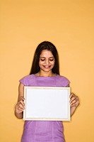 Pretty mid adult Indian woman holding blank sign
