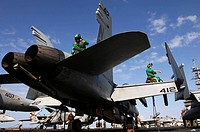 Sailors wipe down an F/A_18 Hornet