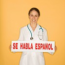 Portrait of Caucasian mid_adult female doctor holding up se habla espanol sign against yellow background smiling and looking at viewer