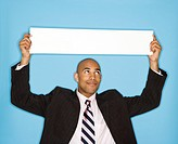 African American man holding blank sign against blue background (thumbnail)