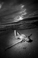 Young Caucasian nude woman wearing lei lying on beach