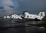 A row of CH_46 Sea Knights sit on the flight line of an air base