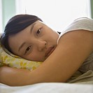 Portrait of pretty young Asian woman lying in bed with head on pillow making eye contact