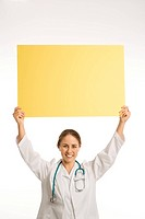 Portrait of Caucasian mid_adult female doctor holding up blank yellow sign smiling and looking at viewer