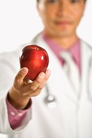 Asian American male doctor holding out apple