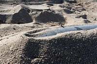 Ordnance shell and a mine lay half_buried in the sand