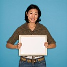 Pretty Asian mid adult woman holding blank sign on blue background