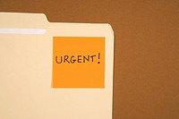 Folder with an orange sticky note attached reading urgent on brown background