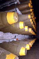 Racks of bombs sit inside the cool, dry interior of a warehouse