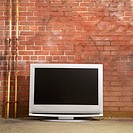 Flat panel television set in front of red brick wall