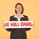 Businesswoman smiling holding sign reading 'se habla espanol.'