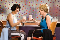 Mature Asian and Caucasian adult females sitting at table in health club cafeteria