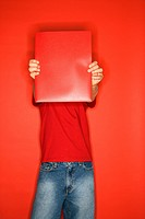 Portait of Caucasian boy covering his face with red folder standing against red background