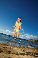 Young adult Asian Filipino female in bikini jumping rope on beach