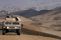 U.S. Army soldier provides security from the gun turret of a humvee