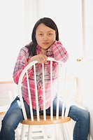 Pretty young Asian woman sitting on chair at table in kitchen