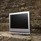 Flat panel television set in front of gray brick wall