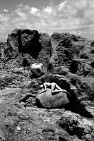 Young adult nude Caucasian woman lying on boulder in rocky landscape