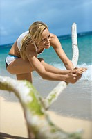Caucasian young adult woman stretching on beach