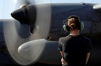 A soldier monitors the performance of a C_130 Hercules engine