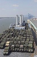 U.S. Army Humvees are loaded onto a docked ship