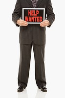Caucasian middle_aged businessman holding help wanted sign