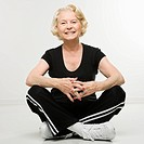 Caucasian senior woman sitting on floor with legs crossed