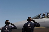 U.S. Air Force Senior Airmen salute the Captain
