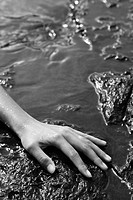Close up of young adult Asian female hand in water on rocks