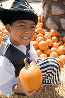 Young boy in pumpkin patch dressed as pirate