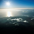 Aerial view of mountainous terrain in Maui, Hawaii with sun shining off the Pacific ocean in background.