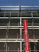 View up scaffolding with red rubble chute prominent