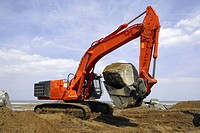 Crawler excavator placing rocks during construction of stone groyne rock armour sea defences