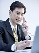 Close_up of businessman holding landing phone and looking down