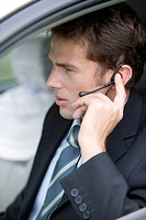 Businessman using cell phone in car, close_up