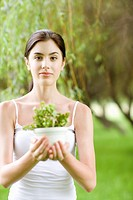 Young woman holding potted plant outdoors