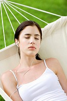 Young woman lying in hammock, eyes closed
