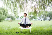 One mid adult man in lotus position sitting on desk outdoors