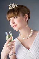 Teenage girl wearing jewelries holding a glass of wine