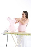 Young pregnant woman holding a pink tutu, standing in front of an ironing board