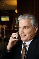 Adult male businessman talking on cell phone in hotel lobby.