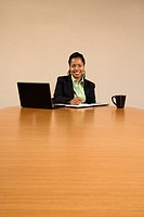 Businesswoman sitting at conference table with laptop computer and coffee cup smiling and writing in book