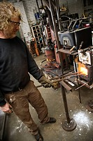 Metal-smith heating metal in forge